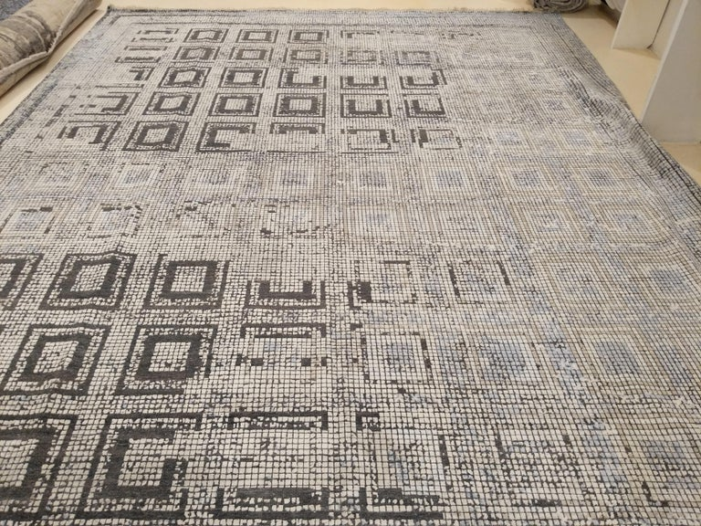 An extremely finely knotted carpet woven completely in pure silk, with a design taken from the floor mosaics of the Byzantine period. The aging effect is obtained by weaving the pattern in a different color and then shearing the pile slightly. This