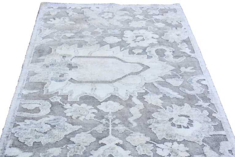 Originating from India, this contemporary rug is hand knotted with oxidized, high quality wool and lustrous silk, complemented by a rare combination of traditional Agra floral designs transitioning into the plush border.