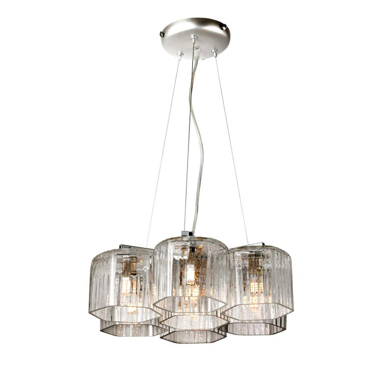 Hanging from thin stay rods that connect it to the ceiling mount, the prized frame of this chandelier is crafted of satin silver and comprises square arms sustaining the seven lampshades in transparent glass with a hexagonal base that in turn hosts