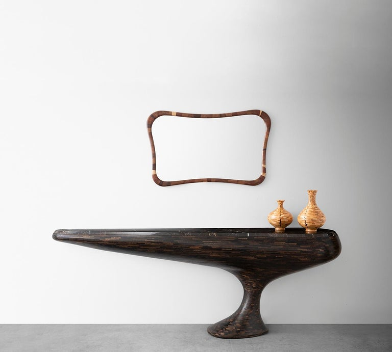 """Part of Richard Haining's Stacked collection, this Console Table has a stance similar to a grand """"hood ornament"""" from a classic car with it's elongated but balanced symmetry solidly perched on a single foot. The thousands of tiny blocks of wood were"""