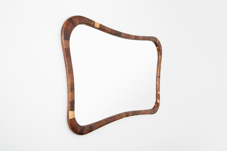 The mirror's frame has been hand-built. Stacked piece by individual piece, layer upon layer, carefully controlling the profile to create the curved rectilinear profile. The salvaged wood offers one-of-a-kind patterns made brought to life by