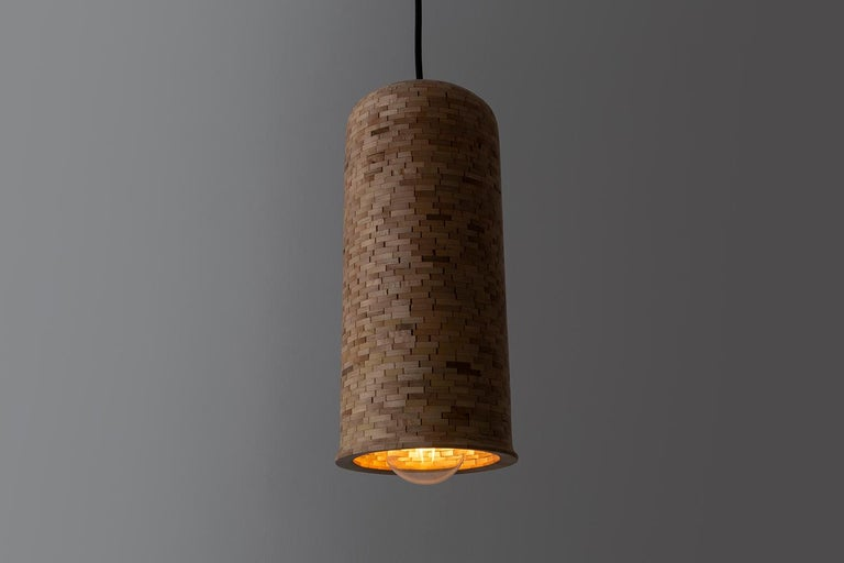 This cylindrical bell-shaped pendant is shown here in salvaged Maple. Each shade is hand-built. Stacked piece by piece, 1/4