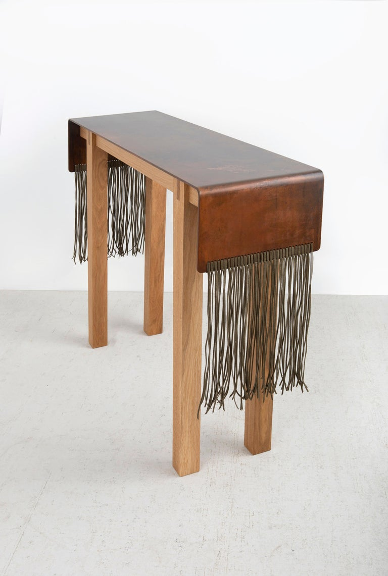 The Native Series debuted in Design Miami 2020. Inspired by the past and present the console as shown is made with an aged patina finished steel plate draped over the sides with soft olive green suede lace. The legs and apron are made of natural