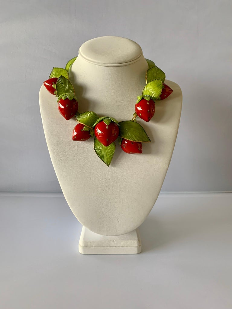 Light and easy to wear, the contemporary handmade adjustable artisanal necklace was made in Paris by Cilea. The statement necklace features seven red enameline (enamel and resin composite) strawberries. The strawberries differ size and feature