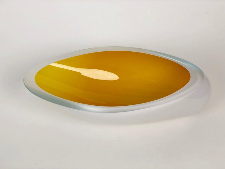 Contemporary studio glass bowl handmade in the Czech Republic. The color is made up of two layers applied to the inside, first white and then yellow. The body is clear glass and the opening has been ground flat on the wheel. The combination of