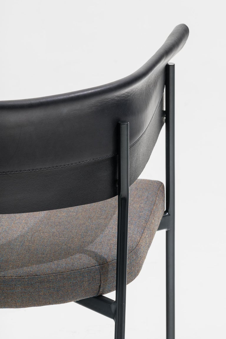 Lounge armchair made with a thin and elegant hand-welded steel frame whose curvature supports the precious leather, folded and sewn to act as a backrest and the same time as an armrest. Available in red, blue, black structure as per the full grain