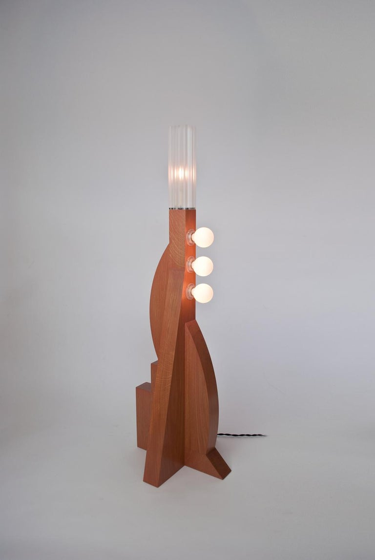 The Tower floor lamp V2 is a One-off design by Louis Jobst. It has an asymmetric solid oak base made up from harmonised geometric forms with a Terracotta finish. The design echoes postmodernist, Memphis design with multiple bulbs and bold shapes and
