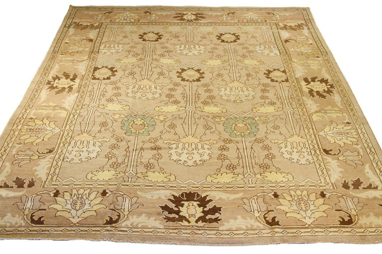 Contemporary handmade Turkish area rug from high-quality sheep's wool and colored with eco-friendly vegetable dyes that are proven safe for humans and pets alike. It's a Donegal design showcasing an ivory field with beautiful beige and brown floral