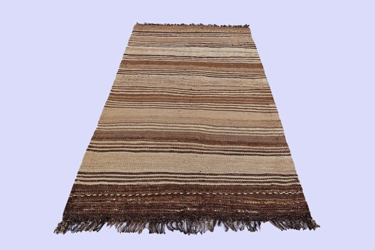 Contemporary Turkish rug handwoven from the finest sheep's wool and colored with all-natural vegetable dyes that are safe for humans and pets. It's a traditional Kilim flat-weave design featuring brown stripes on a beige field. It's a stunning piece