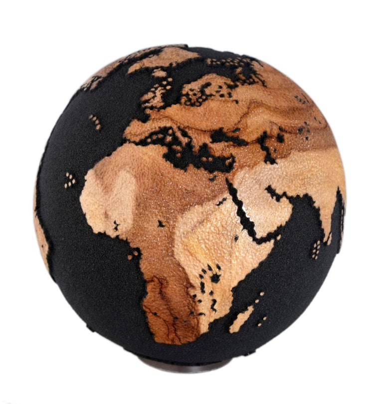 Contemporary wooden globe made of hand-carved teak root and volcanic sand with hammered skin texture finishing  Dimension: 7.87 In / 20 cm Materials: Reclaimed teak root, volcanic sand finishing, mounted on aluminium bearing for easy rotation,