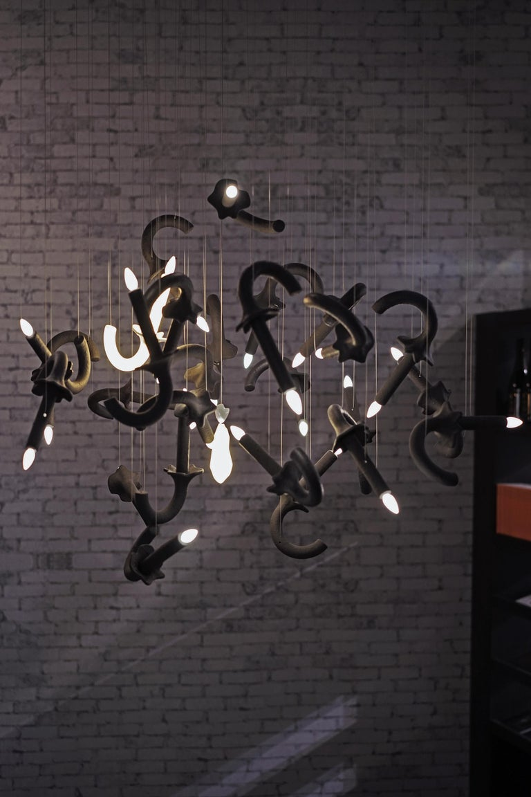 The Wersailles Carbone Déconstuit bespoke chandelier is designed by Sylvie Maréchal and it is entirely manufactured in France. This chandelier is made of 27 Limoges Porcelain Carbone (black painted) candleholders, 1 Limoges Porcelain white