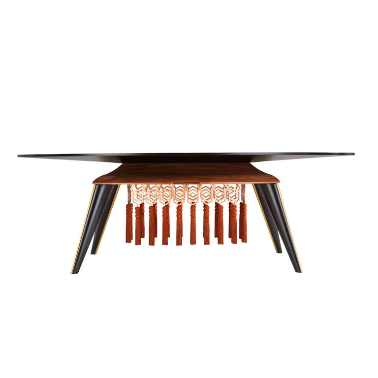 Butterflies flutter on this tabletop, getting lost in the hexagonal decorations that characterize this collection. Adorned with tassels and copper decorations, the table can seat 4-6 people. Top with inlay in white/black wood veneer with copper