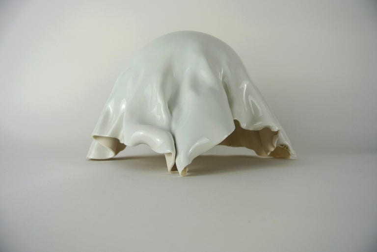 Contemporary, white porcelain object with white glossy glaze hand-crafted by Danish Artist Christine Roland.  A one-of-a-kind folded object, glazed only on the outside.