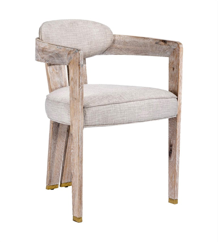 A set of 4 elegantly, handcrafted dining chairs finished in whitewashed oak with a seat upholstered in natural cream linen.  Each seat features a sleek silhouette and brass detailing making each chair a perfect sculptural piece that fits