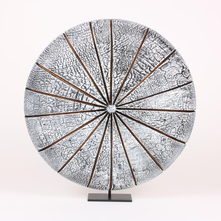 Beautifully textured contemporary white wood sculpture in the shape of a disk on a metal stand. Artist Natacha Heitz finds the primary material for her extraordinary crackled wood sculpture in the Arolla pine. After turning her wood to form