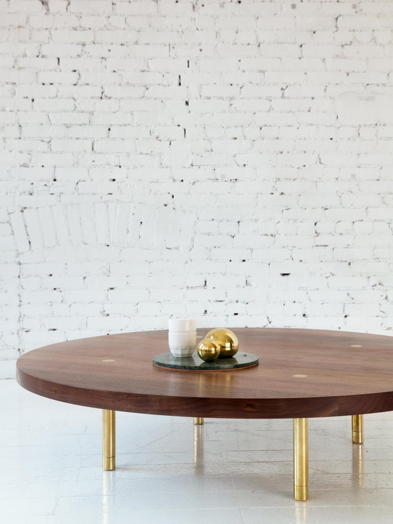 This contemporary, minimal wooden coffee table features a hardwood top and solid brass legs with our signature tenon detail and precision machined leveling feet.  Shown here with a walnut circular top and burnished brass legs. Made to order in