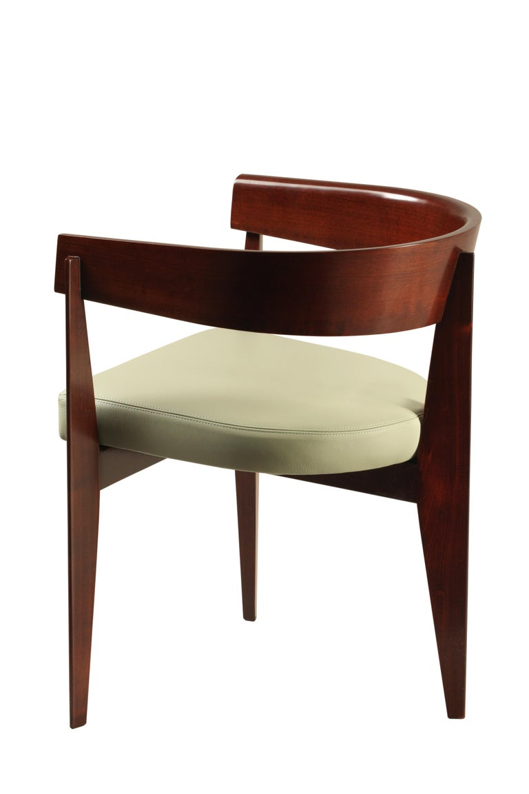 Ronson contemporary upholstered armchair made of cherry wood. The curved backrest is supported by three legs. Padded cushion upholstered with leather or fabric.