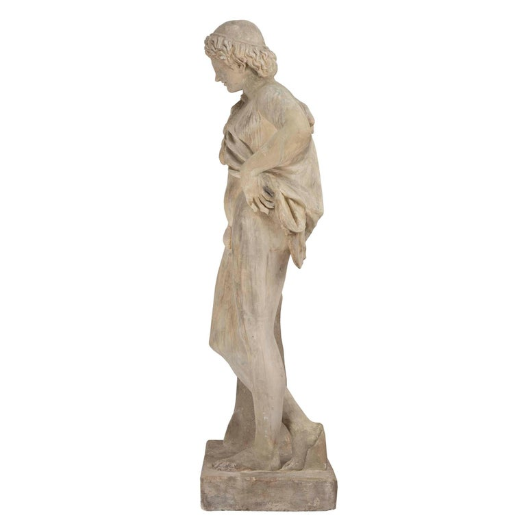 A handsome Continental 19th century plaster statue of a young hunter. The statue is raised on a rectangular base. The nude hunter is leaning on a tree trunk with his spoils draped across his shoulder and his left arm at his hip. Fine details and