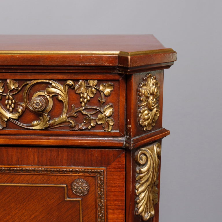 A continental French Louis XV style abattant offers mahogany construction with upper lng drawer having cast bronze scroll and foliate mounts over drop front secretary desk having bookmatched veneering with central hand painted Victory decoration