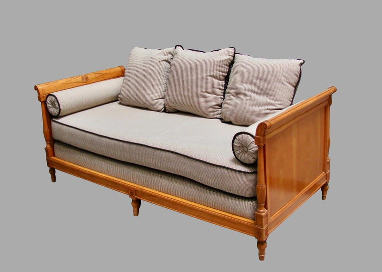 A very pretty Continental fruitwood daybed, the identical paneled sides with carved lozenge framed bosses and columns ending in square carved blocks above reeded toupie feet. Upholstered in blue and white cotton fabric with 3 cushions and 2 side