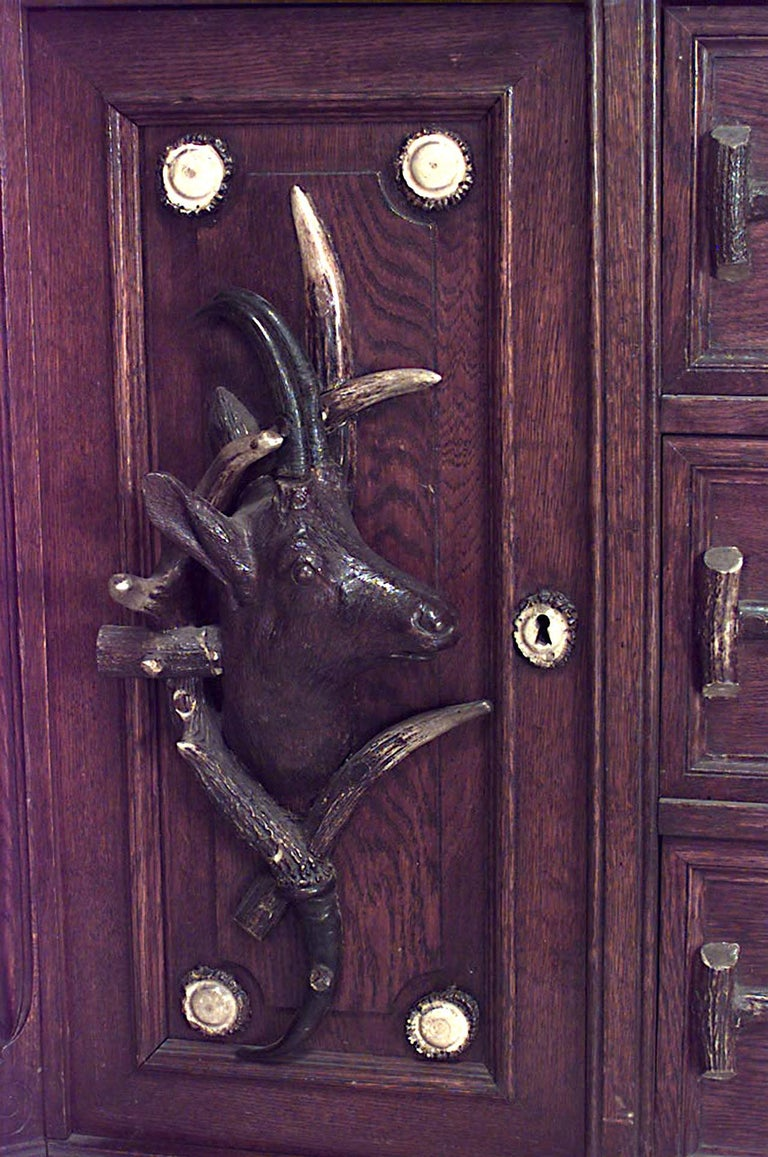 Continental German (19th century) horn and oak bookcase cabinet with deer head carved doors and pediment.