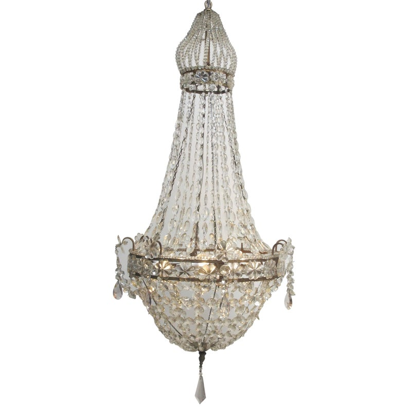 Unique gilt iron and large faceted crystal chandelier with beaded bell shape cage at the top continuing down to strands of graduated and faceted square crystals to an gilt Iron frame with large glass rosettes and accented with amethyst drops.