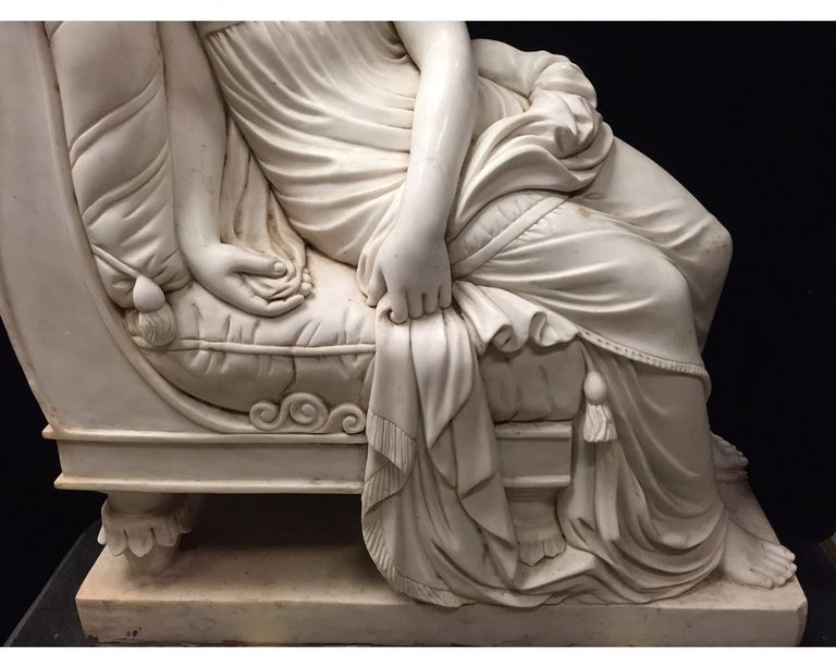 Monumental continental hand carved marble figure of a reclining maiden in classical robes seated on a traditional European recamier cushioned with tassels, all raised on a rectangular marble plinth. 20th century. Meticulous attention was given to