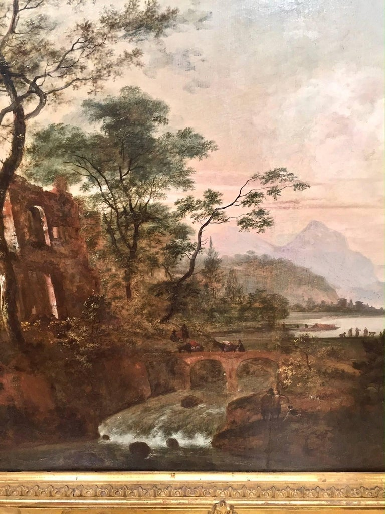A very pretty late 18th or early 19th century continental oil on wood panel landscape painting depicting a pastoral water scene with a carriage crossing a bridge, the well-painted scene with ruins and people in a forest and mountainous background.