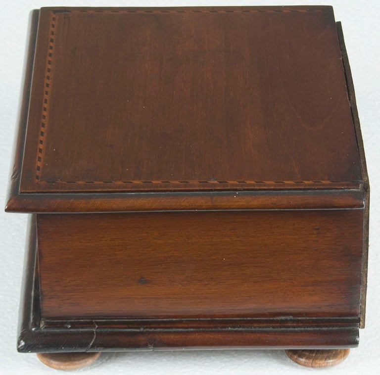 This stunning antique jewelry box is the perfect small gift for someone or for yourself! The box is mahogany wood with satinwood and ebony inlays. A single drawer is fitted with a brass ring pull and lined with green felt. Also it is joined with