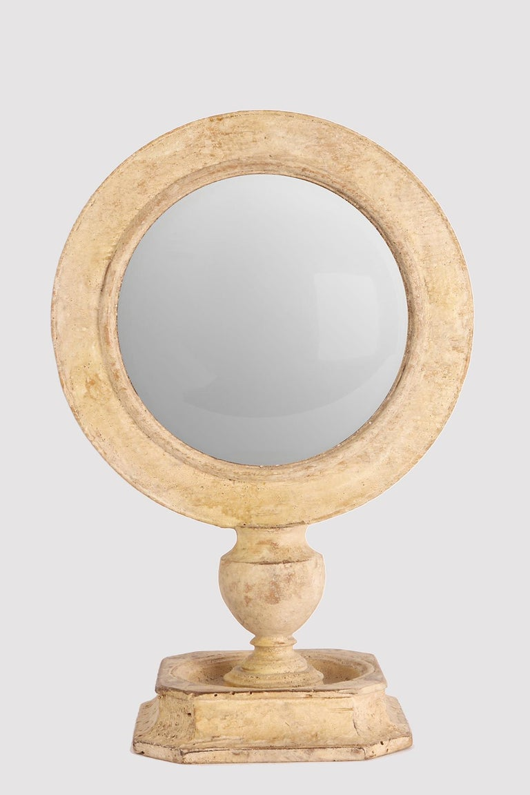 A Wunderkammer round convex mirror with white wooden frames mounted over a white wooden square base on the rear of the frame there is one round paesina stone. Italy, 1870 ca.