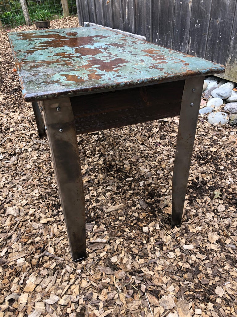 A one of a kind industrial table having wooden top with copper tones underneath a distressed turquoise paint. The legs are aluminum and give a great looking contrast to the top.