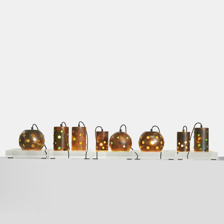 Copper and glass pendants by Nanny Still A collection of 8 copper and glass pendants with yellow, gold, and green glass. The bubbles are created by being blown into an oxidized copper spherical or cylindrical shell. They are rewired in black cord.