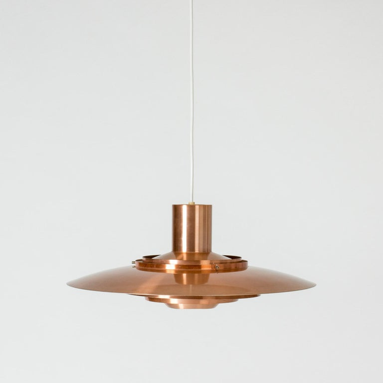 Sleek copper pendant lamp by Jørgen Kastholm and Preben Fabricius. Cool silhouette and wonderful, warm glow.