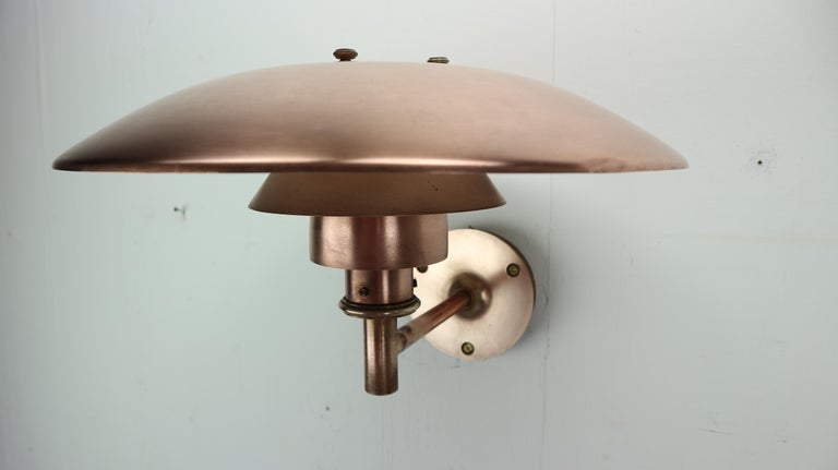 This unique wall lamp is designed by Poul Henningsen for Louis Poulsen in 1960 circa and made in Denmark. Copper lamp is having age-related patina. The lamp's design is based on the IDEA of a set of reflective shades which create balanced,