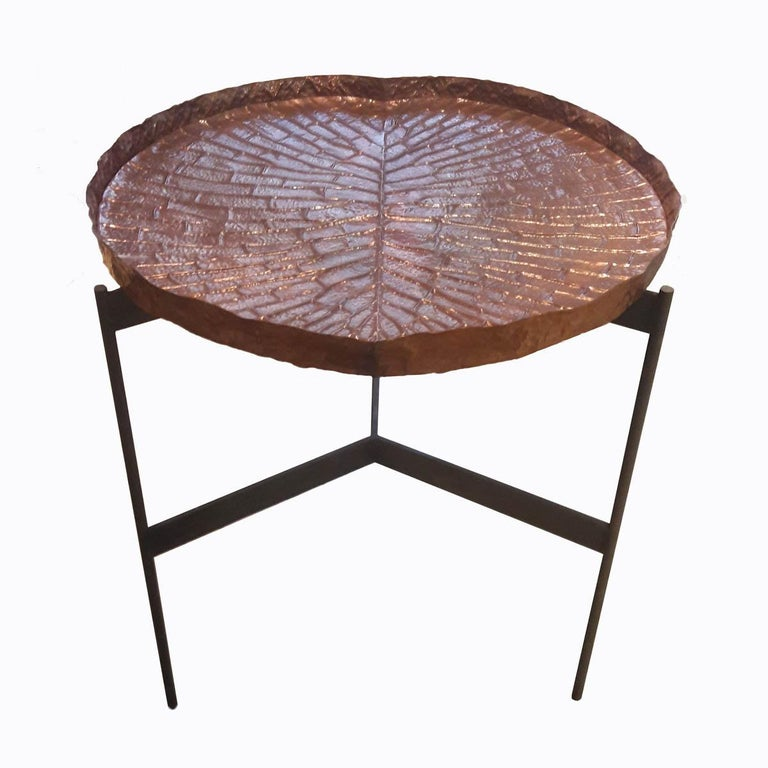 A high table with a repoussé copper tray resembling a lily leaf, on top of a wrought iron base. From Indonesia. Its unique looks and sleek, stylized lines make this original table an eye-catching addition for a porch, a patio, or any other space for