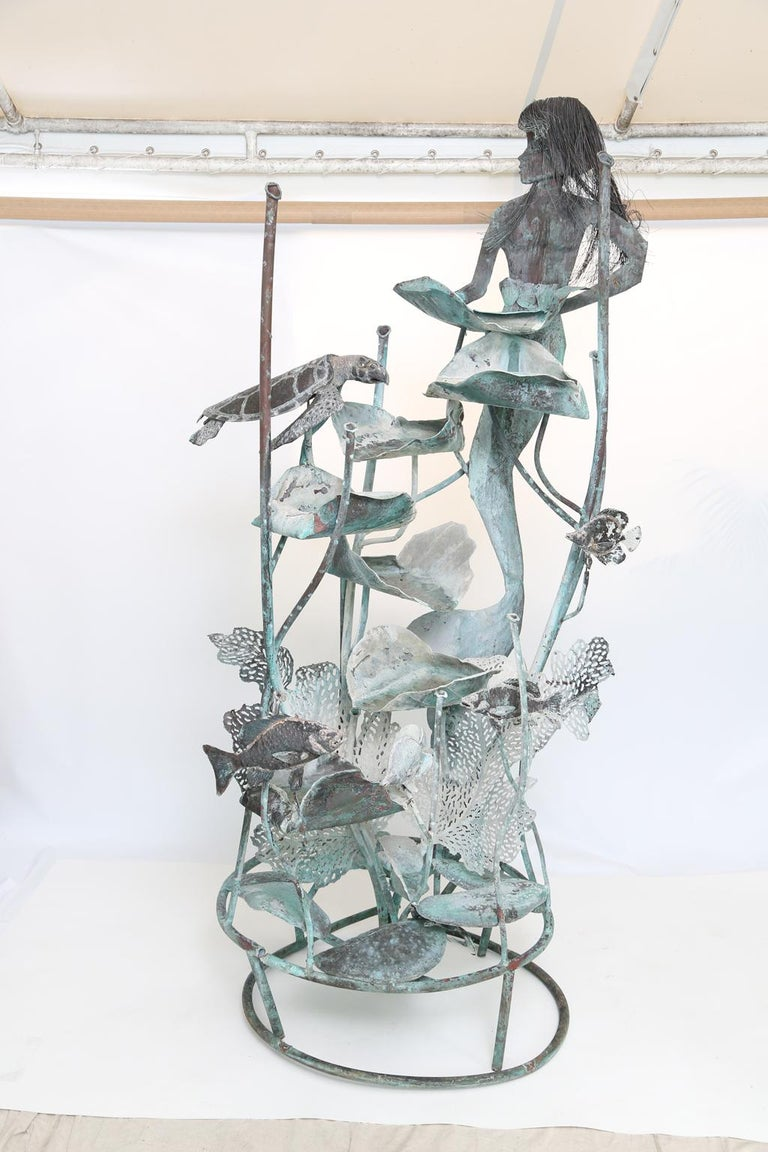 Whimsical fountain sculpture, of copper, by metal artist Glen Mayo; its mermaid focal point holding a leaf which cascades water down the fountain, among turtles, angel fish, other sea life, and coral.   Stock ID: D2499.