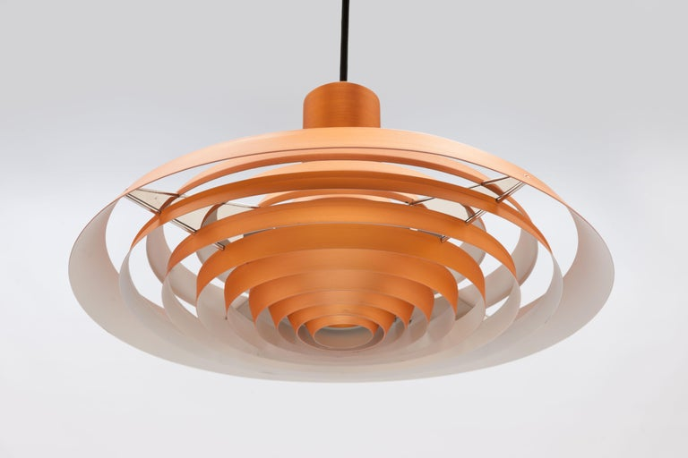 Copper Langelinie plate pendant by Poul Henningsen for Louis Poulsen originally designed in 1958 for the Langelinie Pavilion in Copenhagen and inspired by the pattern of rings in the water surrounding the Pavilion. This lamp was produced in the same