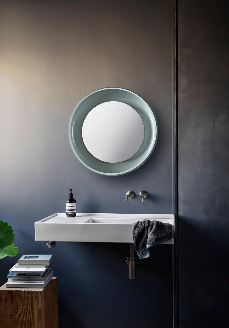 Coque has a taste for dynamic, rich contrasts. The mirror is protected by a ceramic shell, which embraces two opposing finishes: glossy and matt. The inner surface is enamelled and shiny, while the outer skin is textured. The mirror is transformed
