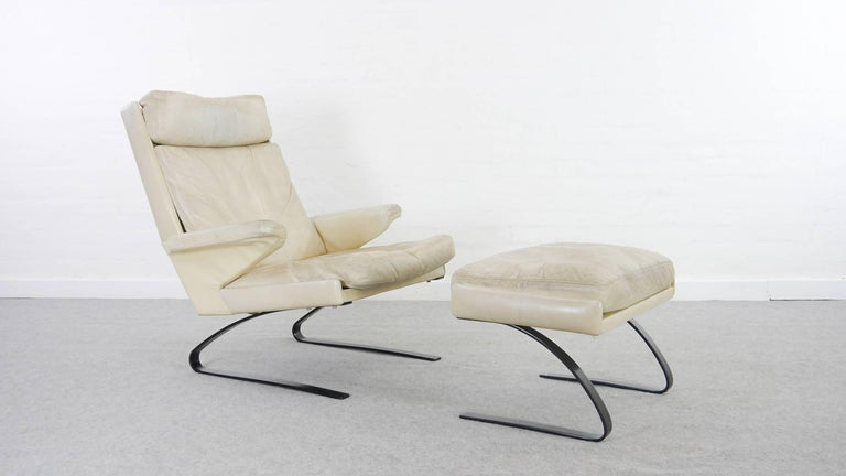 COR swing lounge chair with footrest. Designed 1972 by Reinhold Adolf and Hans-Jürgen Schröpfer. Marked with COR-Sticker. Unusual black colored metal base. Upholstered in original white, off-white leather. Comfortable and minimalistic.