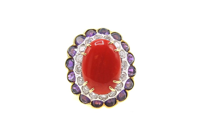 This extravagant 1980s cocktail ring features an oxtail-blood red oval coral that is measured to be approximately 12.5 carats. At a slight angle 16 bright white and sparkly round brilliant cut diamonds are bezel set in white gold and surround the