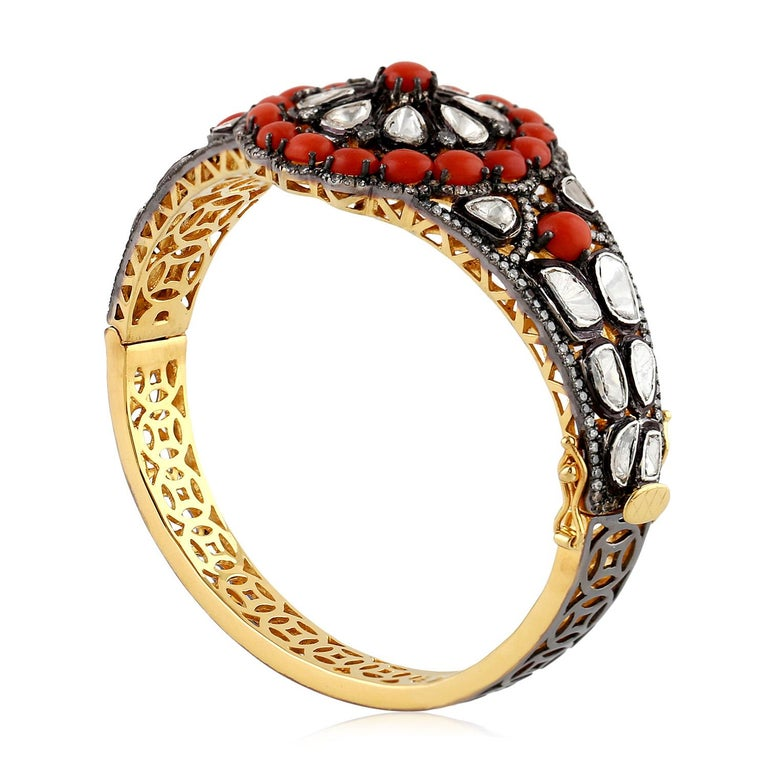 Pretty in coral, this floral designer bangle in rosecut diamond and coral is perfect for any occasion. As this bangle is openbale and oval in shape it sits on the wrist perfectly.  Closure: Box Clasp with safety clasp  18KT: 2.284gms Diamond: