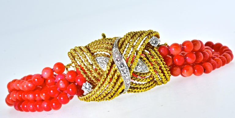 Coral beads, bright red/orange come together with an elaborate  18K gold  twisted motif clasp. Fine white diamonds are set through out in platinum, these diamonds are estimated to weigh .68 cts., they are H/I in color (near colorless), and very