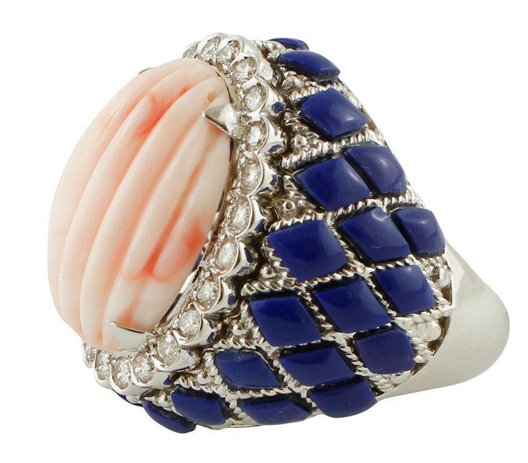 Cocktail ring in 14k white gold structure, mounted with a central finely carved pink coral secundum surrounded by a crown of diamonds and decoration of lapis lazuli. The origin of this ring goes back to the 1980s, it was totally handmade by Italian