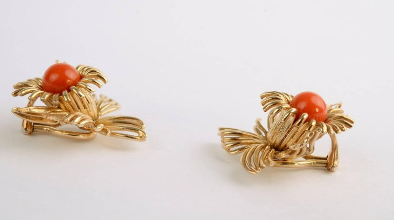Graceful and airy floral earrings with a central cabochon coral stone, The earrings have wonderful dimensionality . Although they are 1 1/4 inches in all directions, they do not appear overly large because of their openness. Clip backs can be