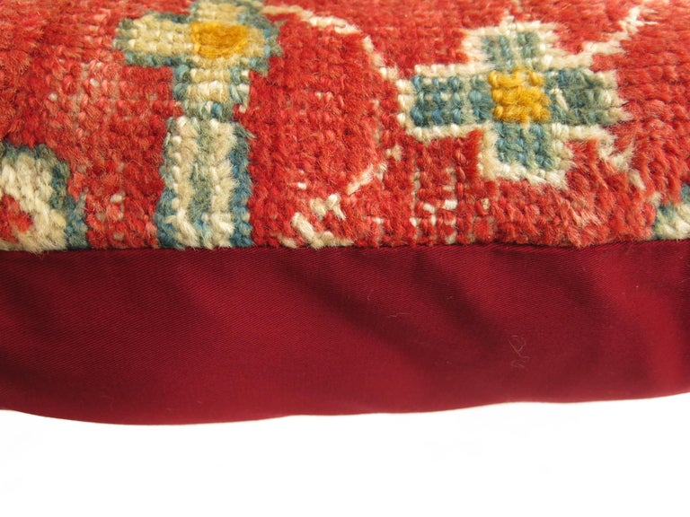 Pillow made from an early 20th century coral and gold color antique Oushak rug