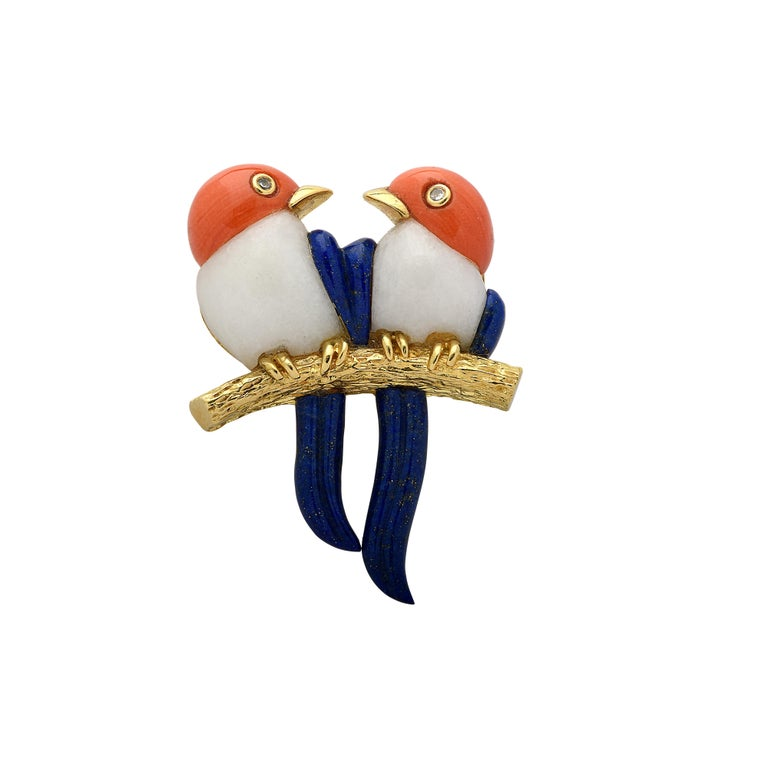 Delightful bird brooch pin crafted in 18 karat yellow gold, depicting an enchanting pair of Lovebirds adorned with coral and lapis with round brilliant cut diamond eyes weighing approximately .02 carats total, G color, VS-SI clarity. This beautiful
