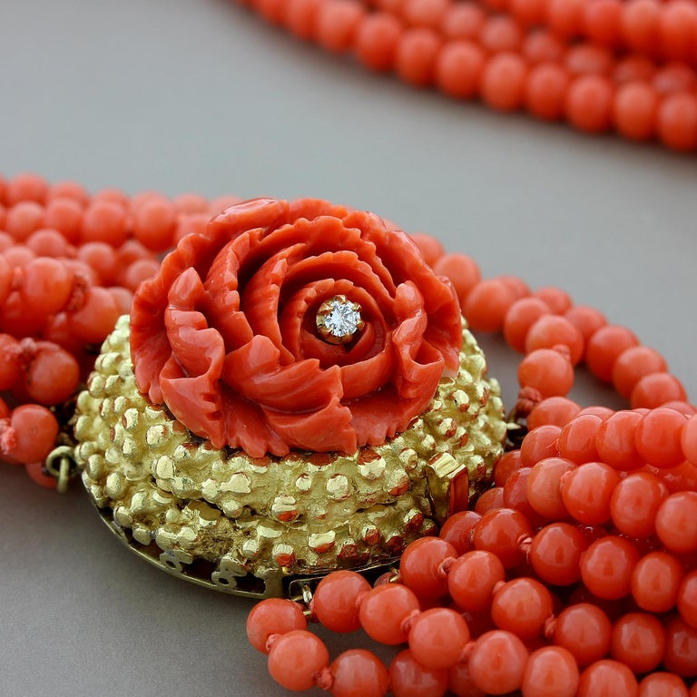 A sophisticated coral necklace accentuated by a coral rosette with a single round cut diamond set in the center. The coral rose sits on a 18K yellow gold mounting which complements the rich red color of the coral. The seamless box clasp ensures for