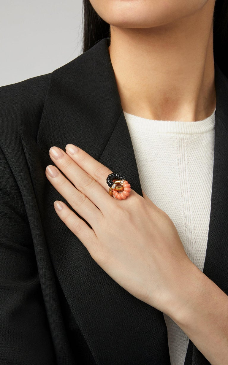 A chic ring in 18kt yellow gold with undulating coral and black onyx, and round diamonds. Made in France, circa 1968.