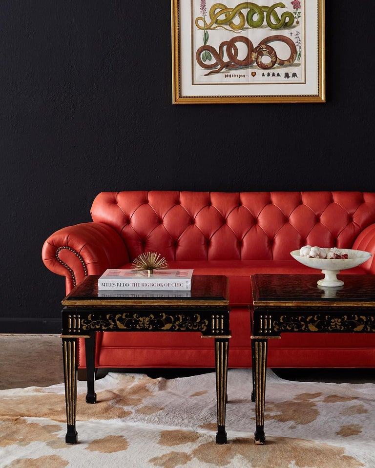Fantastic tufted leather chesterfield sofa settee or loveseat featuring a stylish coral red leather. Deep generous seating area flanked by English style rolled arms with brass nail head trim accents. Constructed with a hardwood frame and upholstered