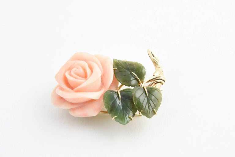 Carved angel skin coral rose with three carved jade leaves mounted in 14K yellow gold. Marked